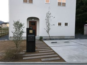 白い壁に映える門柱と緑のアンサンブル